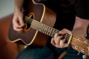 Mann spielt Westerngitarre