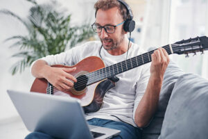 Mann lernt Gitarre auf dem Sofa