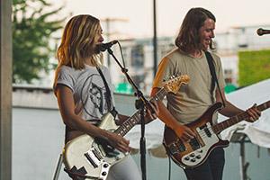 Mann und Frau spielen Gitarre auf Bühne